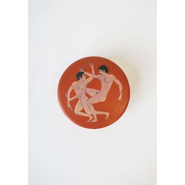 A chic round box, decorative or jewelry, with Greco-Roman nude male figurative design, circa 20th century. Boxes exterior...