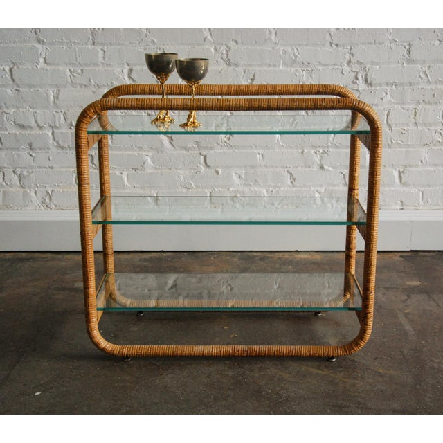 A fine and superbly crafted rattan and glass etagere. The shelves are three-eights inch thick glass and in excellent...