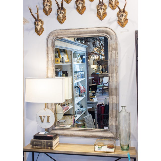 This antique French Louis Philippe mirror came to us with a very distressed gilt finish. We had it refinished in a hand...
