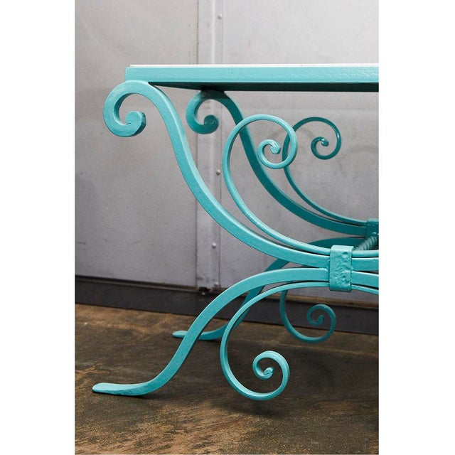 The wrought iron base of this garden table has been powder coated in a nice bright turquoise color. The small table has a...