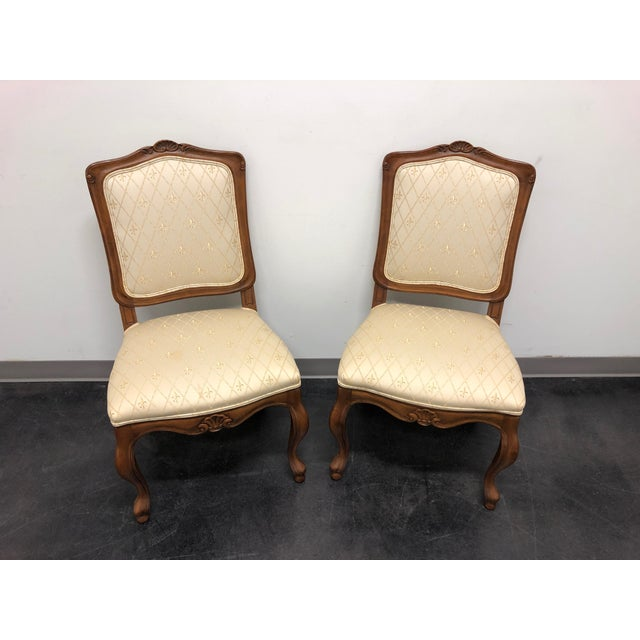 A pair of dining side chairs by Baker Furniture Company. Made in the USA in the late 20th Century. Walnut. Overall: 22w...