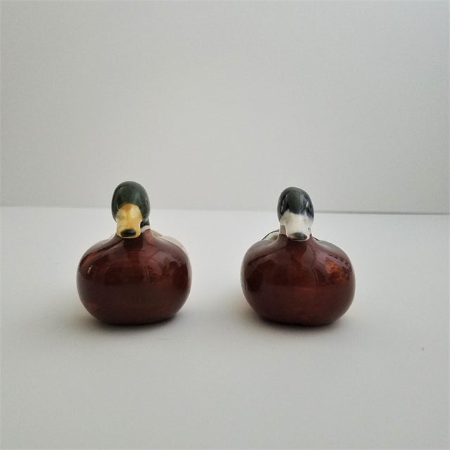 Two vintage hand-painted, ceramic mallard duck figurines. Figurines are hollow with an opening on the back. Each mallard...