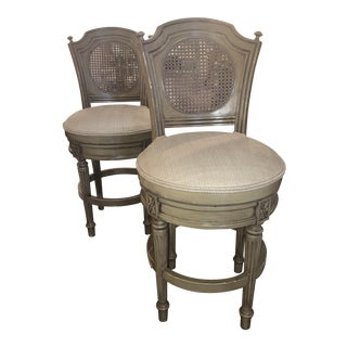 Late 20th C Wood Taupe Painted Swiveling Bar Stools With Cane Backs, Round Cushioned Seats and 4 Legs With Carved Ridges & Flowerets - a Pair For Sale