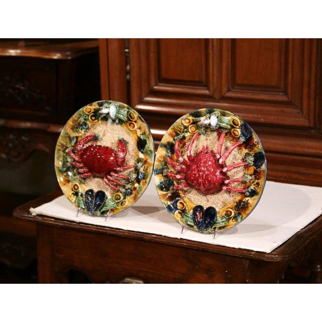 This colorful antique pair of hand-painted majolica decorative wall platters were crafted in Brittany, France, circa 1950....