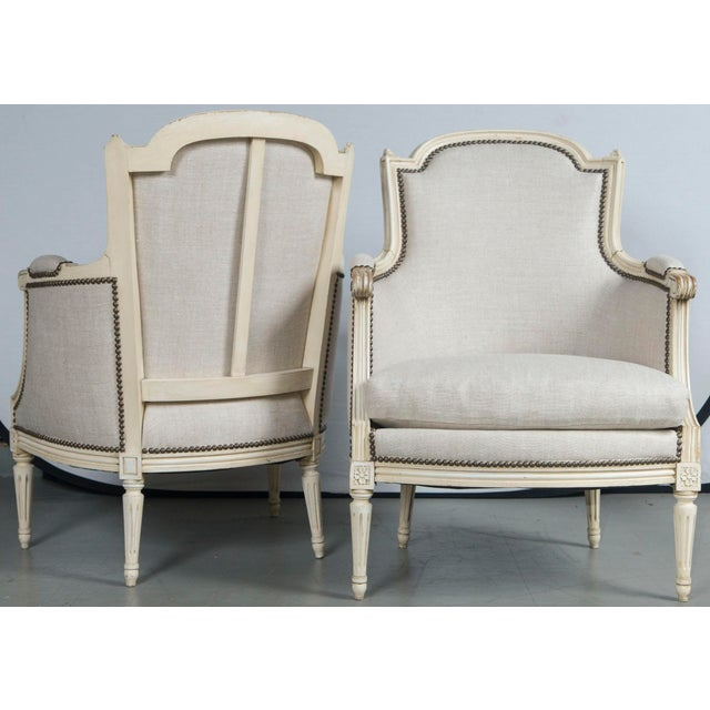 Good pair of Louis XVI style French Bergeres. Newly upholstered in Belgian linen with brass nailheads. Cream color paint...