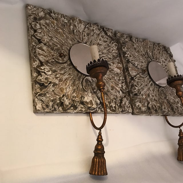 Pair of square carved wood electric wall candle sconces with gilt metal arms, carved tassel, and round mirror back. Chalky...