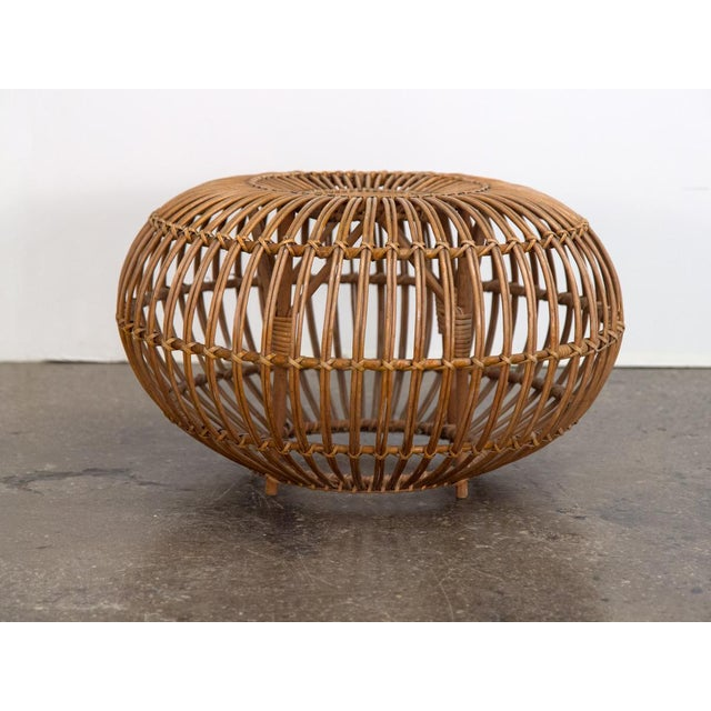 Classic woven rattan Franco Albini foot stool. In overall good condition, the ottoman has some age-appropriate but nothing...