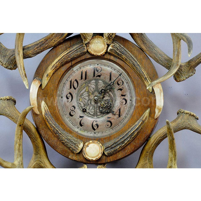 an antique cabin decor antler wall clock. silver plated brass clockface with painted figures. decorated with original...