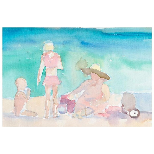 A delicately painted American School watercolor showing a young family seated at the water's edge of a sandy beach and...