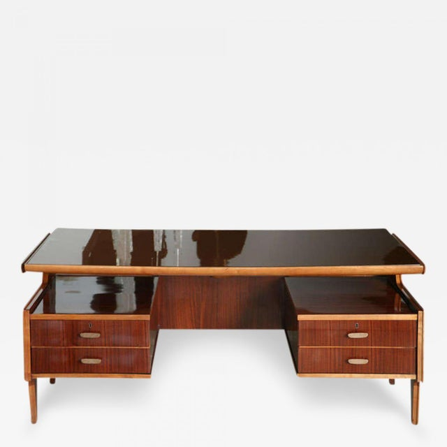 The inset colored glass top above a writing surface cantilevered above four drawers with original hardware, terminating on...