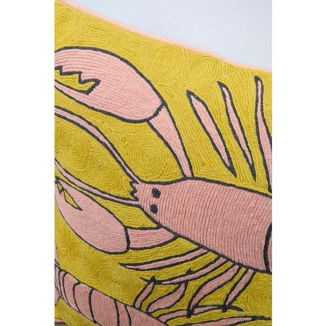 """Featuring a striking palette of mustard yellow and soft pink wool, the Lobster cushion is a playful design and is typical..."