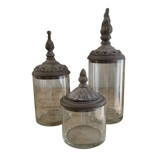 Trio of Glass Apothecary Jars With Decorative Patinated Metal Finial Lids For Sale