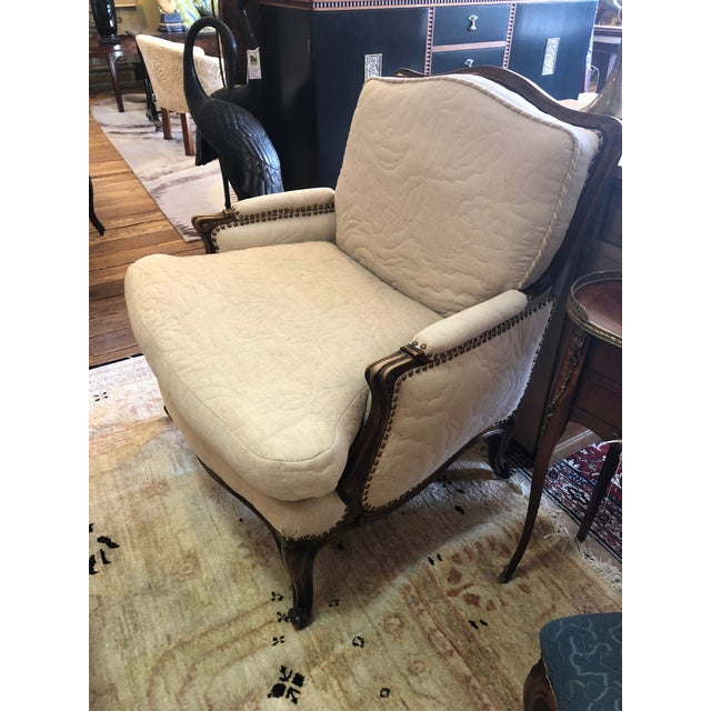 A big comfy neutral French style bergere having handsome carved walnut frame and creamy taupe quilted upholstery front,...