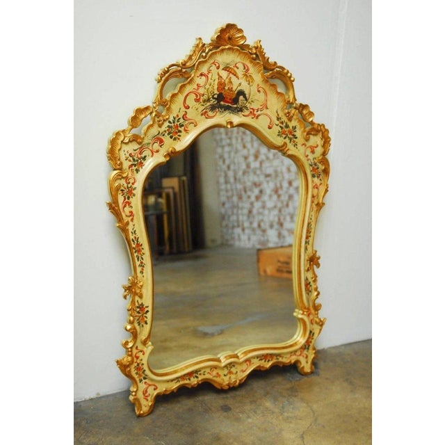 Stunning Italian Venetian style mirror decorated in the chinoiserie taste featuring a hand-carved frame finished with an...