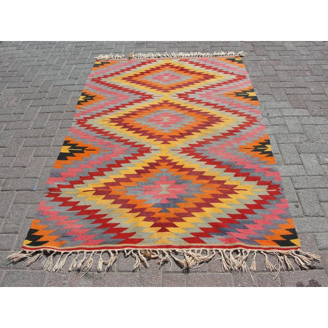 Offered is a vintage handwoven Turkish kilim rug. The kilim is nearly 45 years old. It is handmade, of very fine quality...