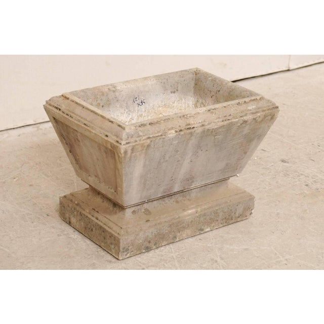 A European stone planter from the early 20th century. This antique, hand-carved stone planter has an overall rectangular-...