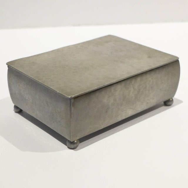 Hand-forged, footed box of hammered pewter with hinged lid and birchwood lining. A sleek casket form adorned only by the...