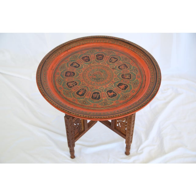 Beautiful hand painted Indian tray with folding hand carved wooden base. Made in the 1960s.