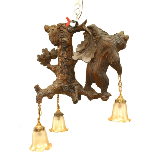 Rustic Black Forest style walnut carved chandelier with a bear figure holding 3 lights from a floral and branch form...