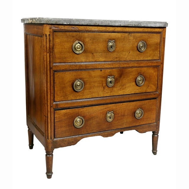 Antique commode with rectangular gray marble top over three drawers each with brass disc and ring handles, raised on...