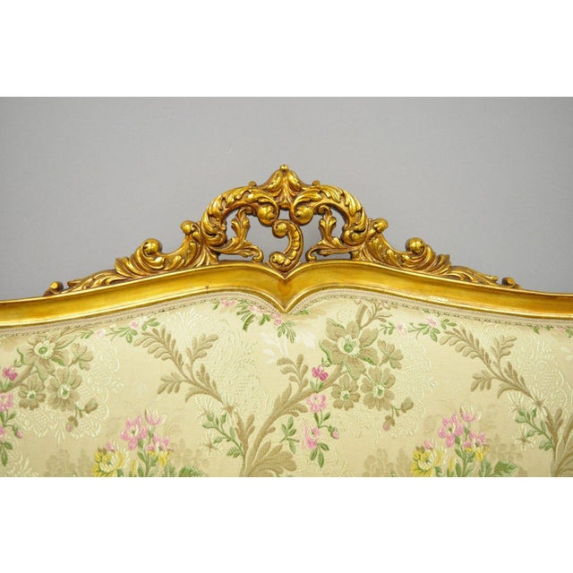 Antique 1920s French Louis XV Style Gold Settee. Item features rolling casters, floral patterned upholstery, solid wood...