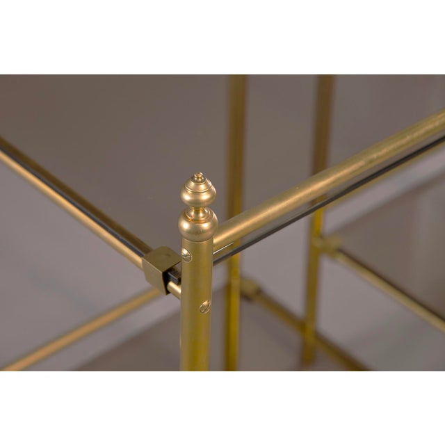 Pair of brass two-tier side tables have smoked glass shelves and tops and decorative finials, circa 1960s. Unknown maker....