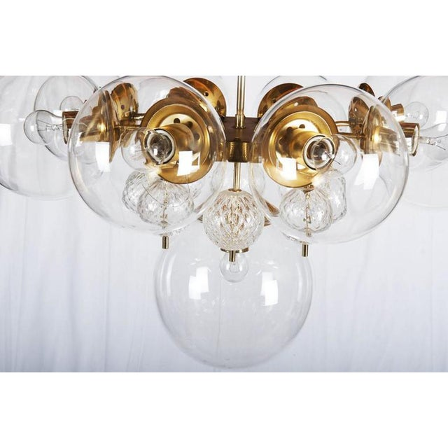 This big brass chandelier, with nine large and eight crystal balls globes, was made by Kamenicky Senov in former...