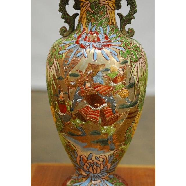 Lovely vintage Japanese vase, hand decorated with raised enamel, polychrome glaze, and gilt, depicting a warrior scene of...