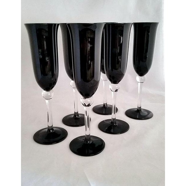 Black tulip shaped crystal champagne flutes. the stem is clear with a ball at the top and tapers down to a black foot....