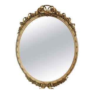French Gilt and Parcel Cream Oval Wall Mirror With Ribbon Tied Crest and Frieze For Sale