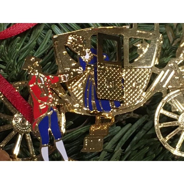 This Ornament depicts a colonial style horse and carriage with a driver and 2 passengers disembarking. A scene from...