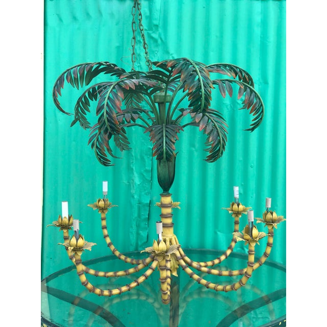 Large and definitely in charge palm leaf and faux bamboo metal chandelier. Minor scuffs and scrapes to the as found...