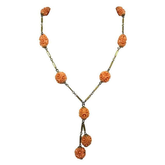 Lovely brass bar link c1920s Y-style necklace embellished with ornate floral design coral-colored celluloid beads. The...