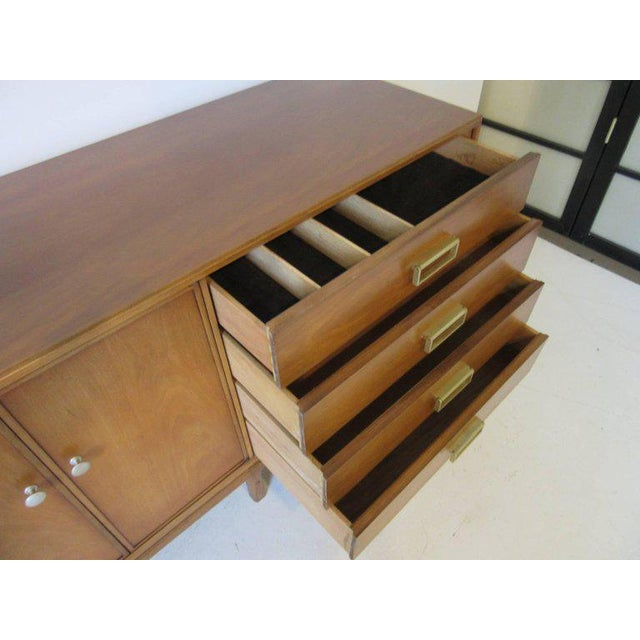 A medium toned mahogany server credenza with brass pulls, lower stretchers and brass details, with double doors, two...