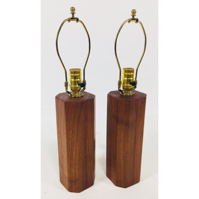 This pair of modern handcrafted lamps are teak wood with hand turned bark wood shades. The shades are light weight paper...