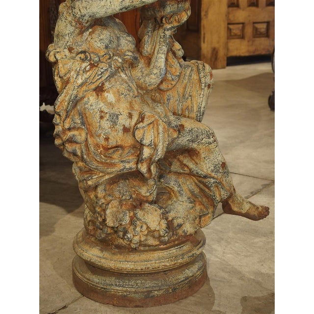 his beautiful pair of cast iron statues date to the early 20th century. Each woman, in robes, sits upon a a wine grape...