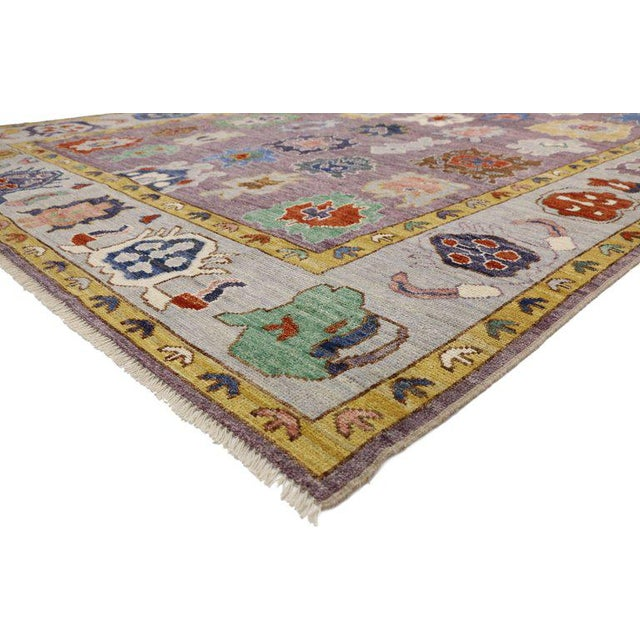 This hand knotted wool contemporary Oushak style rug features an all-over floral pattern spread across an abrashed...
