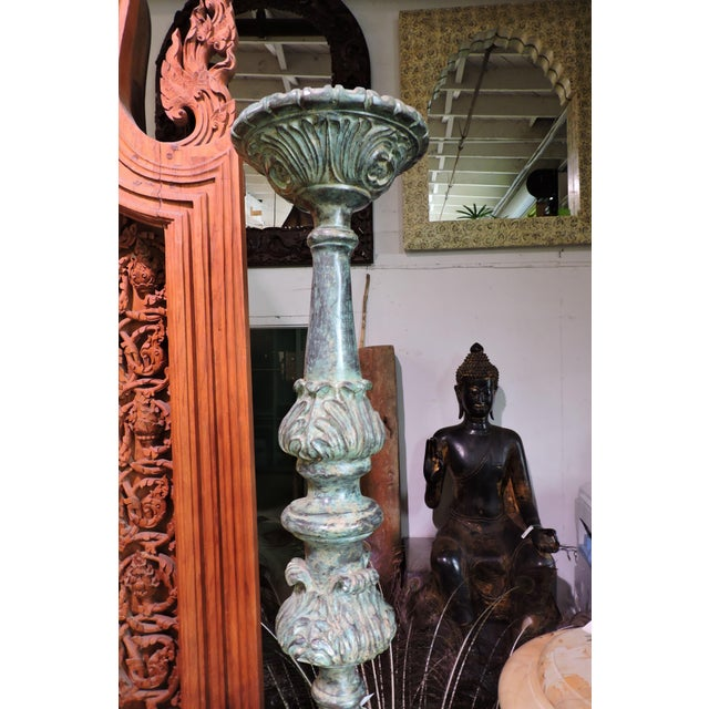 Hyper tall bronze candle holder. Lighting the candle entails a stool or NBA player with matches.