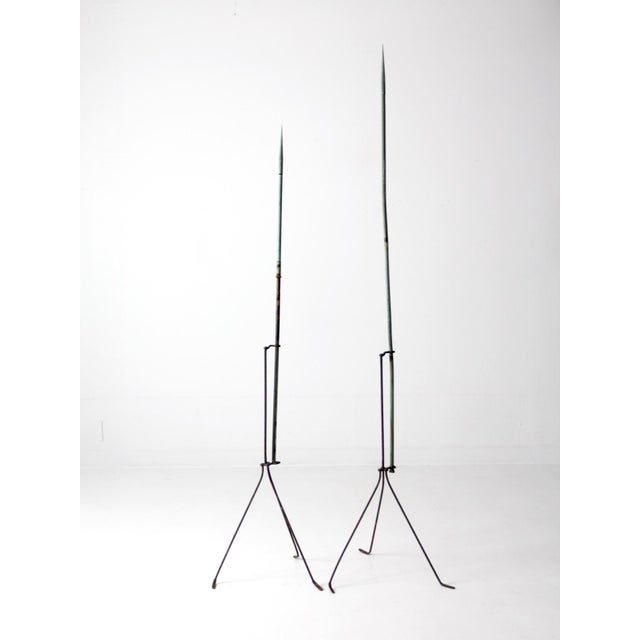 A pair of Victorian lightning rods. The late 19th century lightning rods feature wrought iron tripod bases and slender...