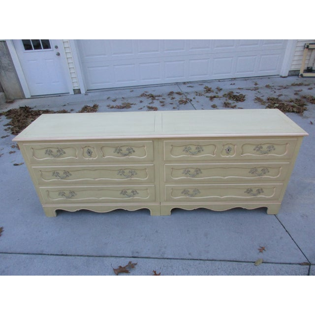 This Baker Furniture side-by-side double chest of drawers is cream colored with faint pink highlights along the edges. It...