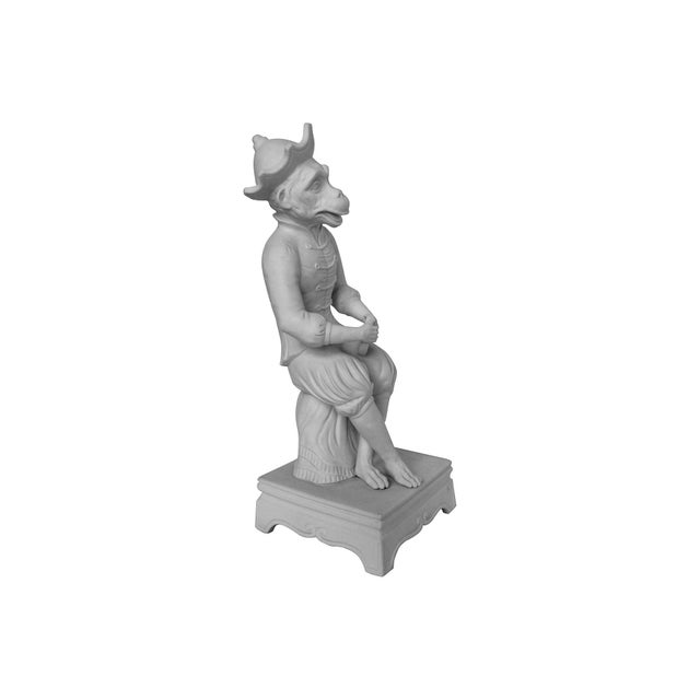 Vintage French parian ware monkey figurine. He is playing a tambourine in a satirical 18th-century singerie style.