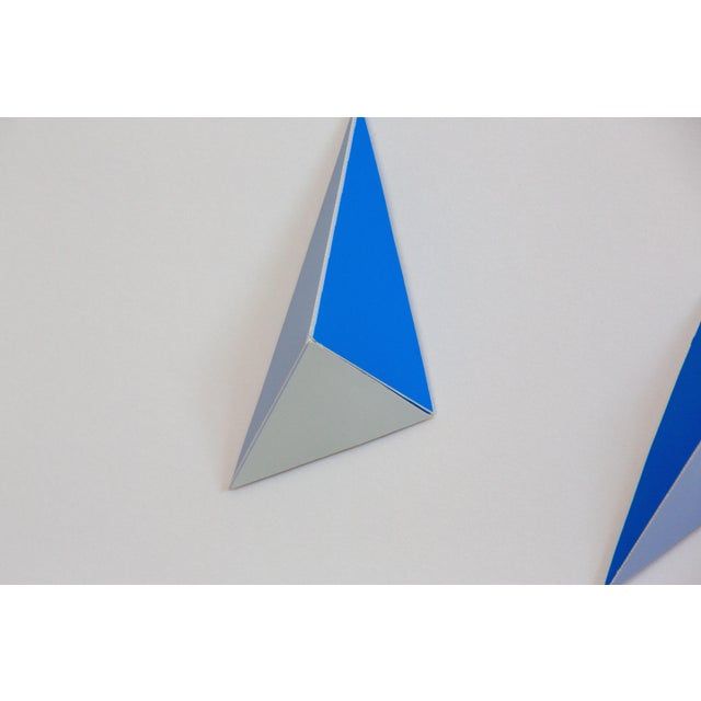Northern Californian artist Dawn Michelle Wolfe cuts and folds pyramid shapes and collages them into a dimensional...