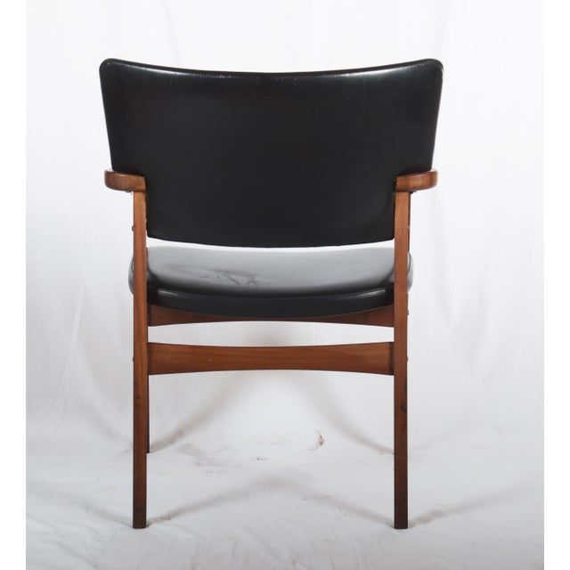 Solid teak frame with upholstered seat and backrest in black leatherette. Made in Denmark in the late 1950s. New...