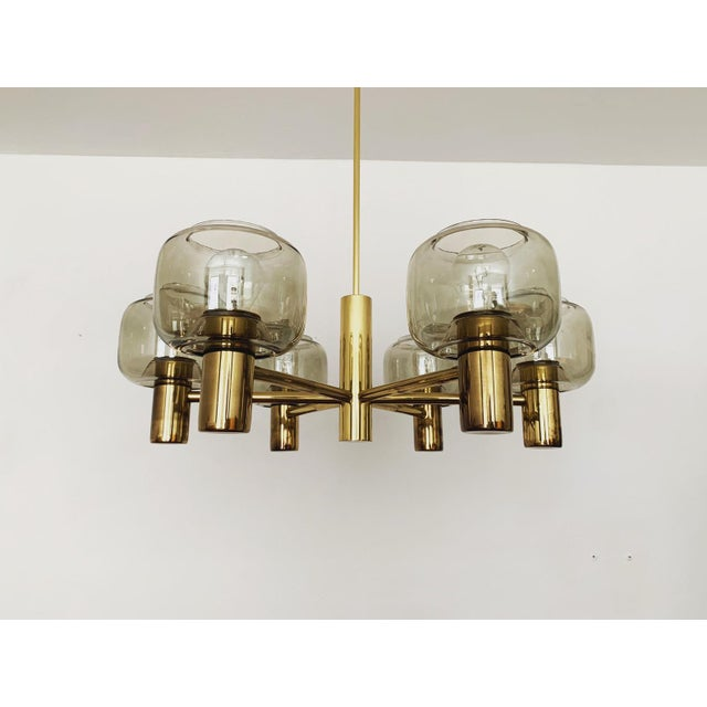 Stunning brass chandelier from the 1960s. The 6 beautifully shaped smoked glass lampshades spread an impressive sparkling...