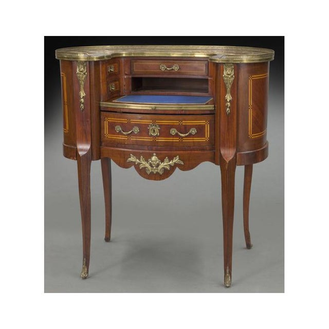 Elegant antique writing desk from France, circa 1900; the kidney shape cabinet features a red marble top with brass...