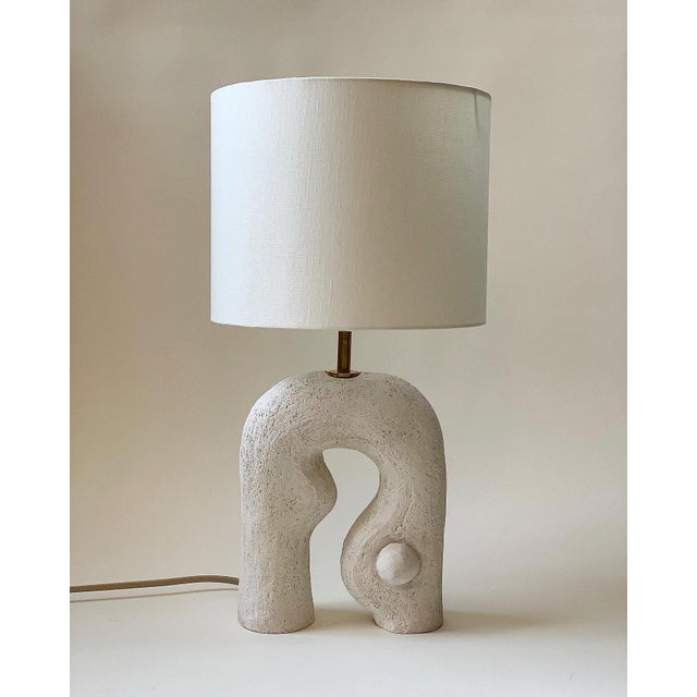 Contemporary ceramic table lamp handmade by artist Analuisa Corrigan. Functional sculpture. Comes with an oyster-hued drum...