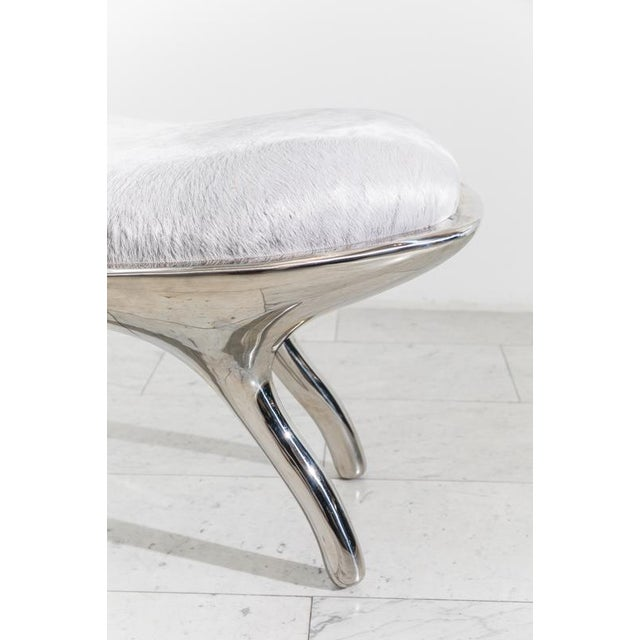 The Biche Bench's muscular sculpted shape is cast in lightweight mirror-polished stainless steel. Upholstered in grey pony...