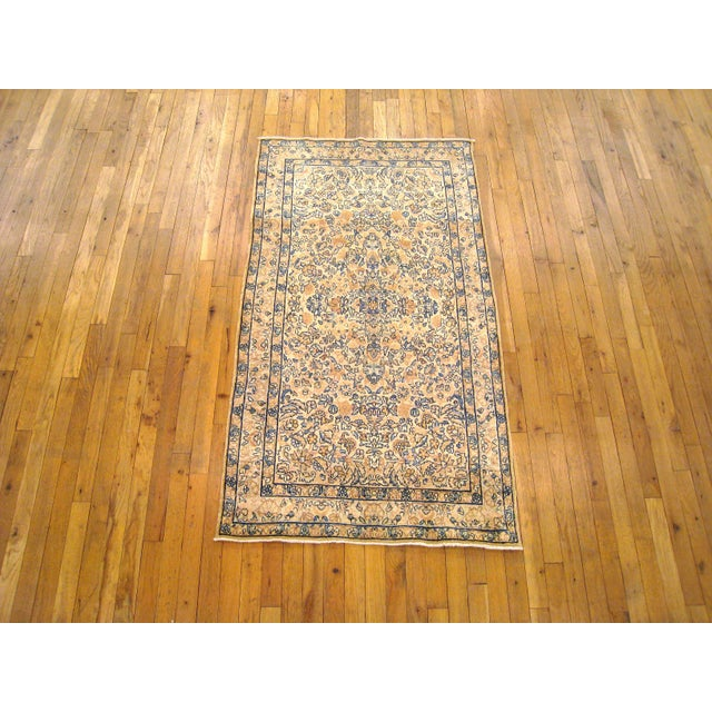A consigned antique Persian Kerman decorative oriental rug, circa 1910. Hand-woven with a short wool pile. Featuring an...