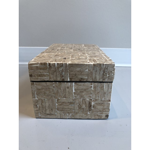 Mother of pearl rectangular pieces creating a larger criss cross pattern on all faces of the box and lid. Interiors of the...