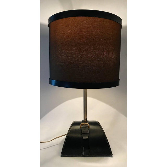 A handsome stitched leather and buckle tables lamp by Jacques Adnet. Includes original stitched leather shade.